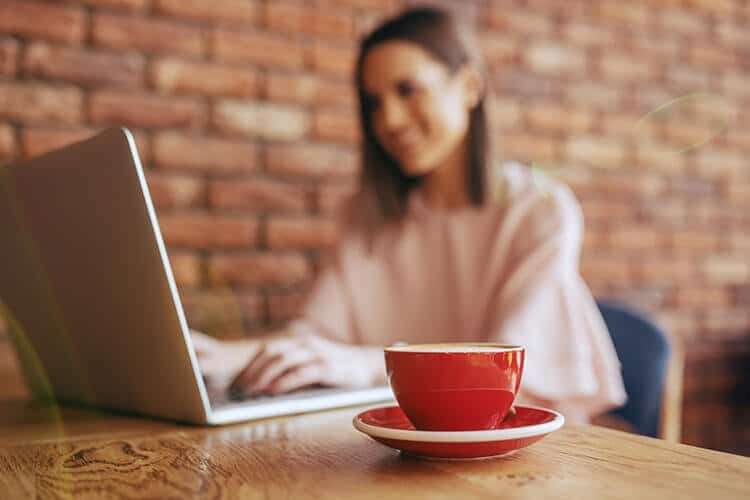 Woman sitting in a coffee shop typing on her laptop with a coffee
