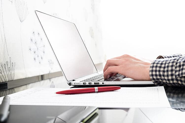 Hands typing on a laptop with a red pen and a white background