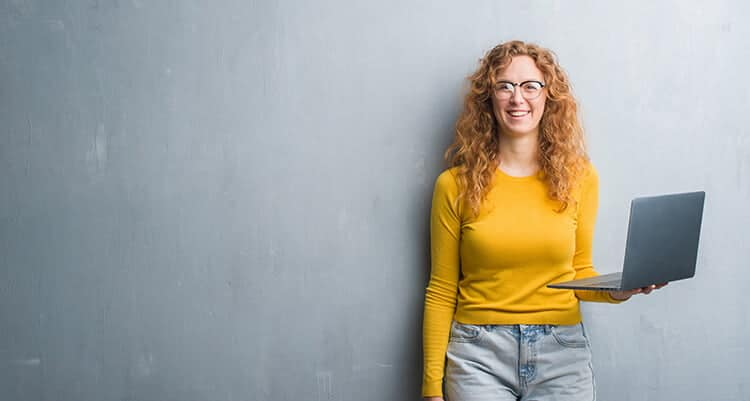 Woman in a yellow sweater standing in front of a grey wall holding an open laptop